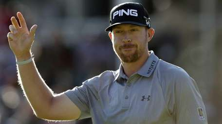 Hunter Mahan waves to fans as he finishes