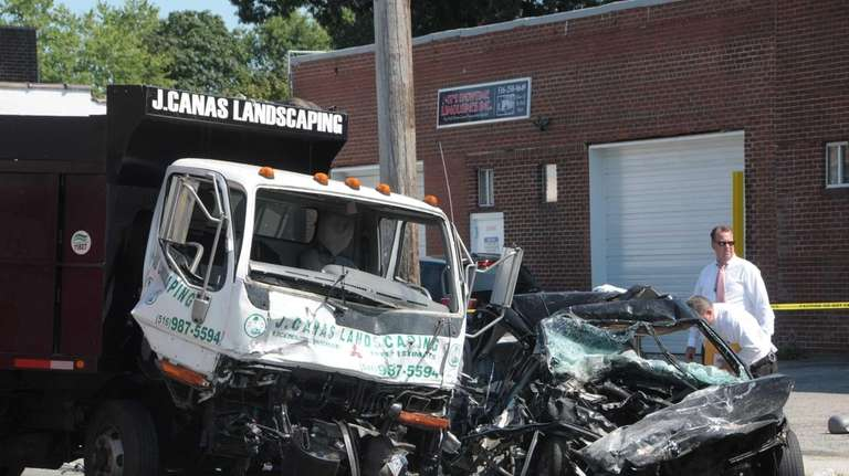 A landscaper's dump truck and a sedan collided