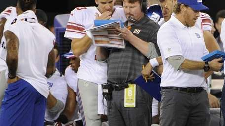 Giants quarterback Eli Manning talks with offensive coordinator