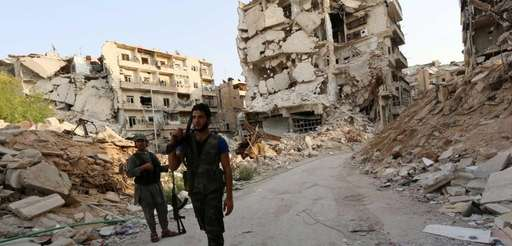 Rebel fighters walk in front of damaged buildings