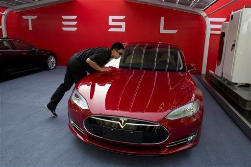 A worker cleans a Tesla Model S sedan
