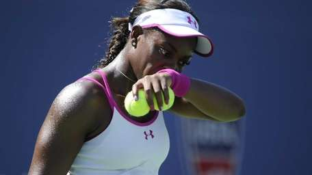 Sloane Stephens wipes sweat from her face during