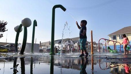 3 year-old Matthew Ramirez enjoys the sprinklers at