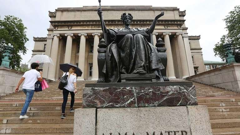 People walk past the Alma Mater statue on