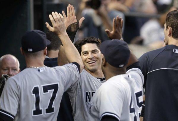 The Yankees' Jacoby Ellsbury, center, celebrates after scoring