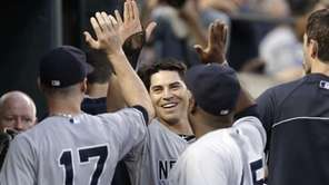 The Yankees' Jacoby Ellsbury, center, celebrates after scoring