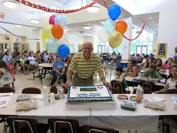 Saul Schachter cuts a cake at a goodbye