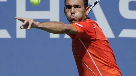 Victor Estrella Burgos returns against Milos Raonic during