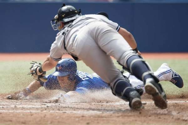 The Toronto Blue Jays' Steve Tolleson, bottom, slides