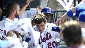 The Mets' Anthony Recker (20) and Dilson Herrara