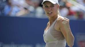 Caroline Wozniacki reacts against Maria Sharapova during a
