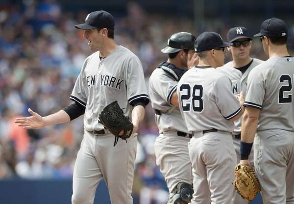 Yankees starting pitcher Brandon McCarthy, left, gestures toward