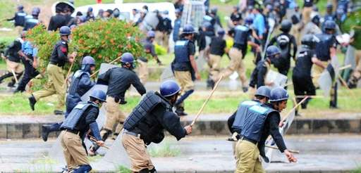 Pakistani police run from opposition protesters during clashes