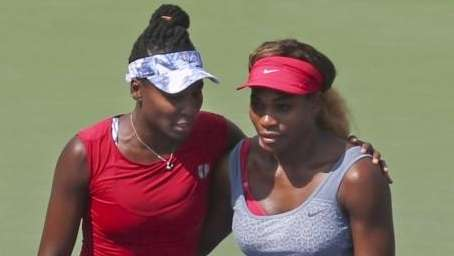 Venus, left, and Serena Williams walk to mid