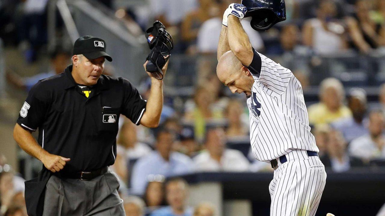 Brett Gardner of the Yankees slams his helmet