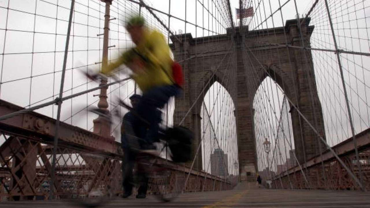 A man bikes on the Brooklyn Bridge.