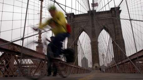 A man bikes on the Brooklyn Bridge.