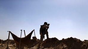 A Kurdish Peshmerga fighter uses binoculars to check