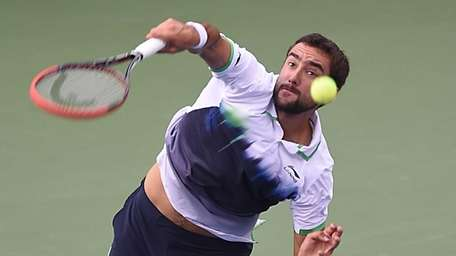 Marin Cilic serves against Roger Federer in the