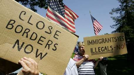 Anti-immigration demonstrators hold signs and American flags during