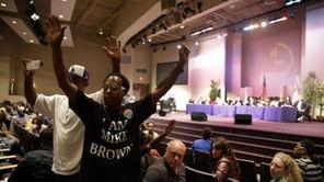 Two men raise their arms during a public