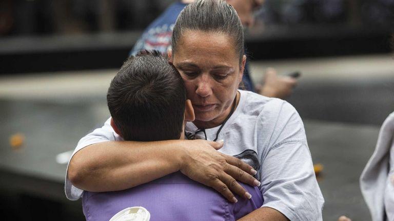 A woman hugs a boy during the memorial