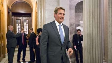 Sen. Jeff Flake, R-Ariz., leaves the Senate Chamber...