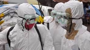 Health workers in protective gear leave after carrying