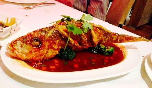 Whole red snapper in sweet-and-sour sauce is served