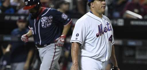Mets starting pitcher Bartolo Colon looks on as