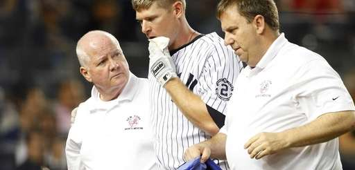 Chase Headley of the Yankees is helped off