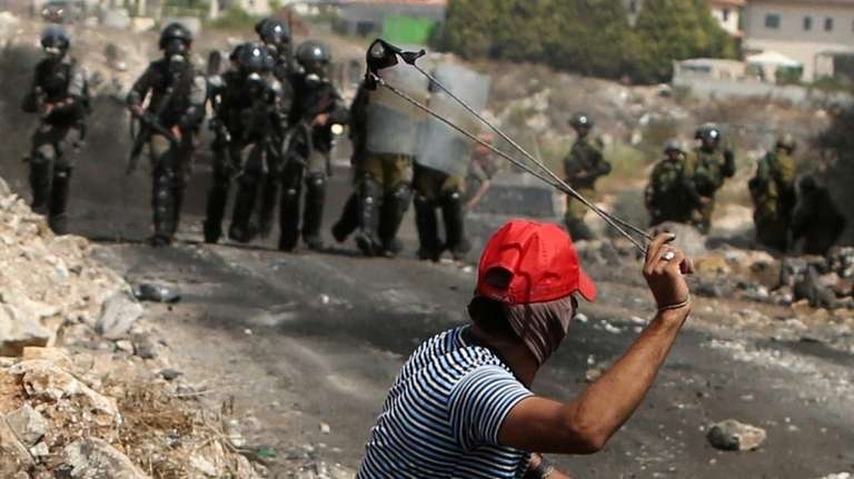 A Palestinian protester uses a slingshot to target