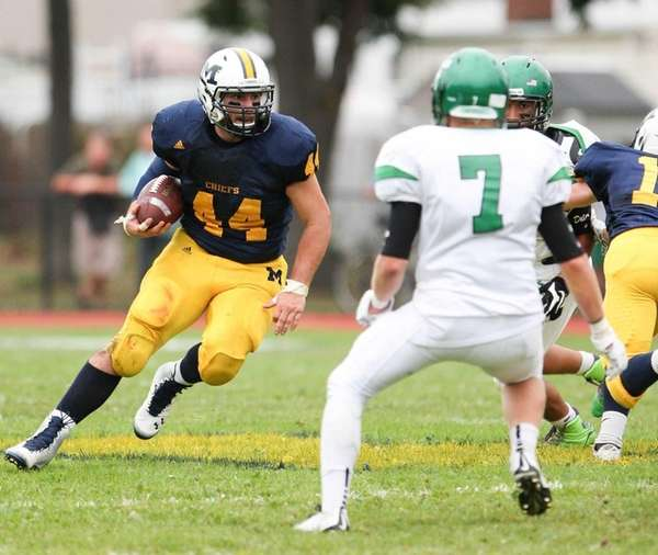 Massapequa's Paul Dilena runs the ball while Farmingdale's