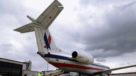 Baggage handlers unload an American Eagle jet on