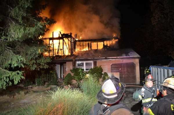 Flames shoot out of a two-story home on