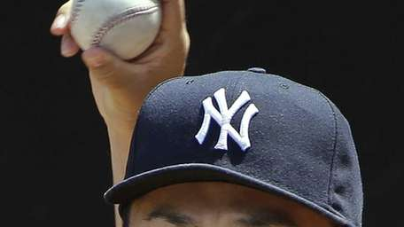 Yankees pitcher Masahiro Tanaka warms up in the