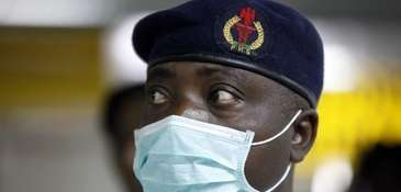 A Nigerian health official wearing a protective mask