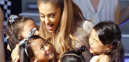 U.S. singer Ariana Grande hugs children during an