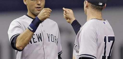 Yankees shortstop Derek Jeter, left, high-fives shortstop Brendan