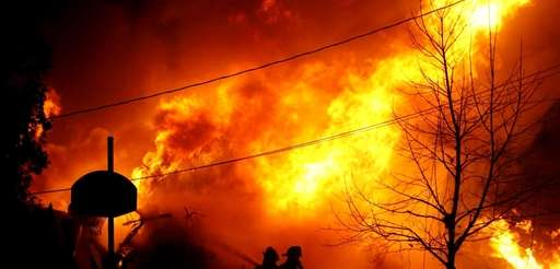 Volunteer firefighters attempt to put out the flames
