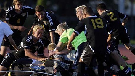 Commack teammates bury Justin Cebollero in the corner