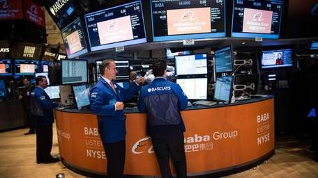 Traders work on the floor of the New