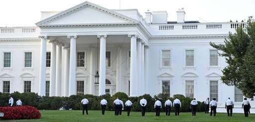 Uniformed Secret Service officers walk along the lawn