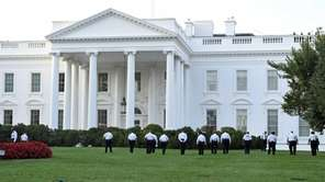 Uniformed Secret Service officers walk along the lawn