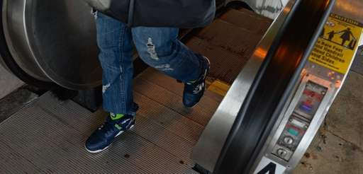 A commuter rides the escalator at the Lindenhurst