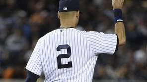 Yankees shortstop Derek Jeter signals two Baltimore Orioles