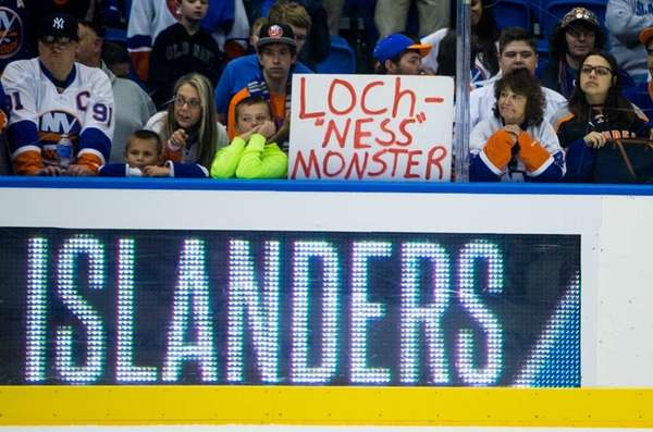 Islanders fans hold up signs before a preseason