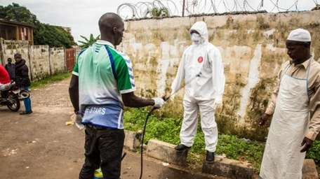 A health worker sprays disinfectant on a person
