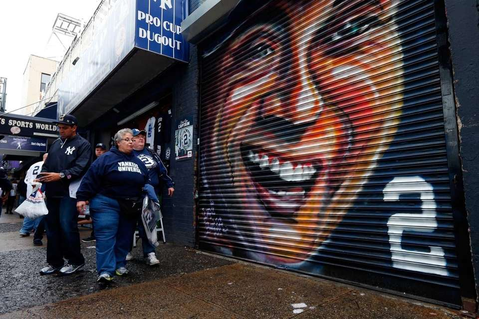 Fans walk past a mural of Derek Jeter