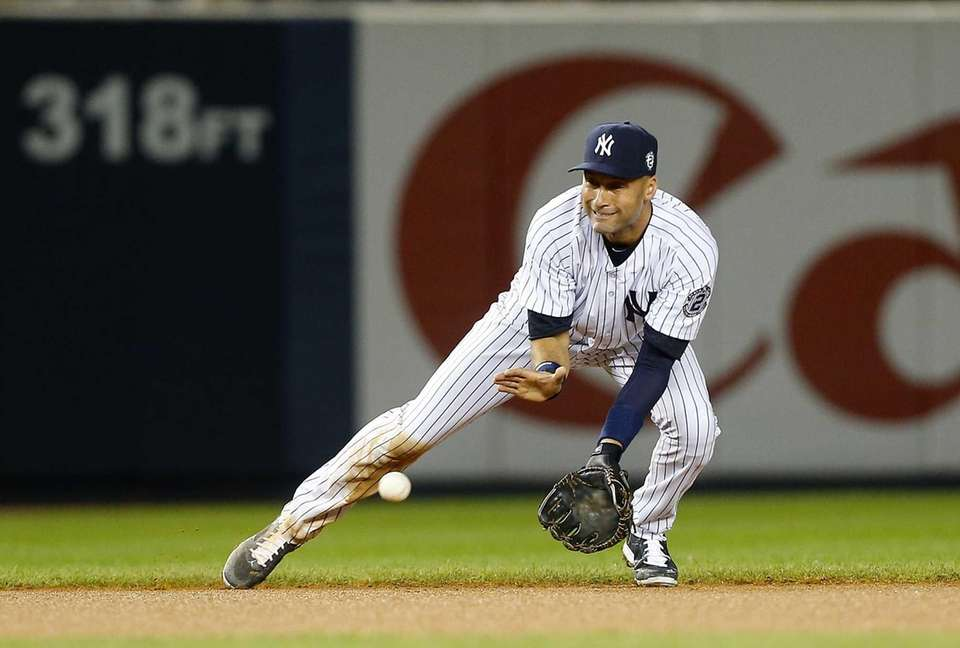 Derek Jeter of the Yankees fields the ball